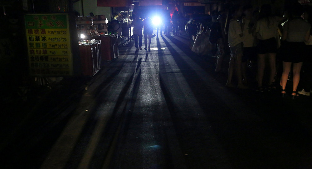 People use flashlights in a street during the blackout that struck Taiwan in August 2017. Photo: Reuters