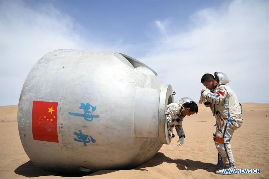 Chinese taikonauts, wearing space suits, are seen getting out of a mock reentry capsule in a desert in northeastern China. Photo: Xinhua