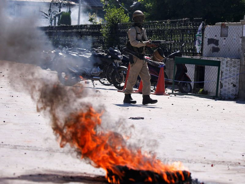 An Indian police officer walks past a burning tire during a protest after Friday prayers in Srinagar on May 25, 2018. Photo: Reuters/Danish Ismail