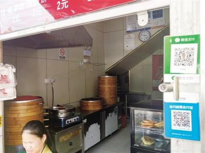 The owner of a breakfast stall was shocked to discover the windfall when checking his AliPay balance. QR codes for mobile payments are displayed at her stall. Photo: Zhengzhou Evening News