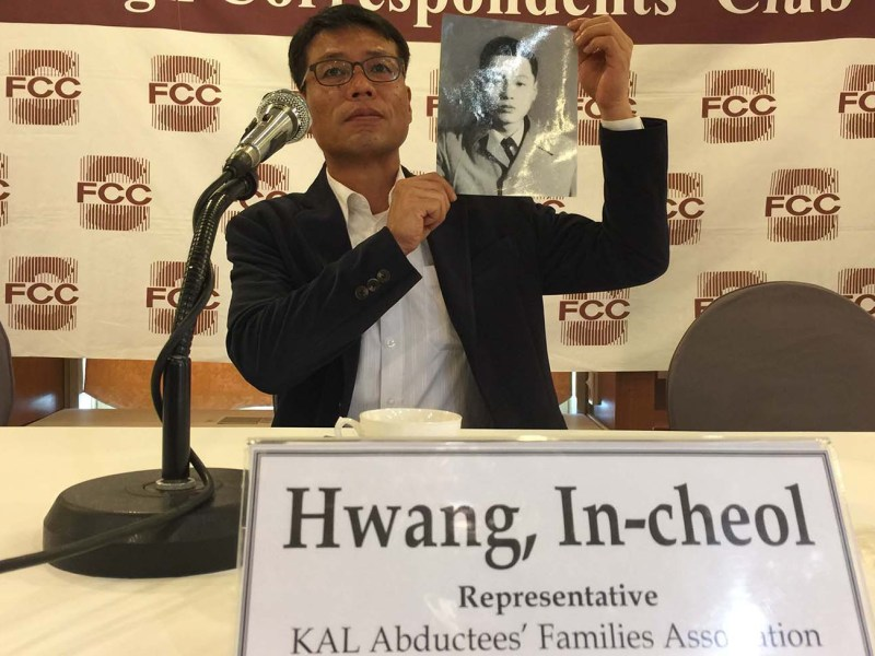 Hwang In-Cheil holds up a photograph of his father, who disappeared when his flight was hijacked to North Korea in 1969. Photo: Asia Times/Andrew Salmon