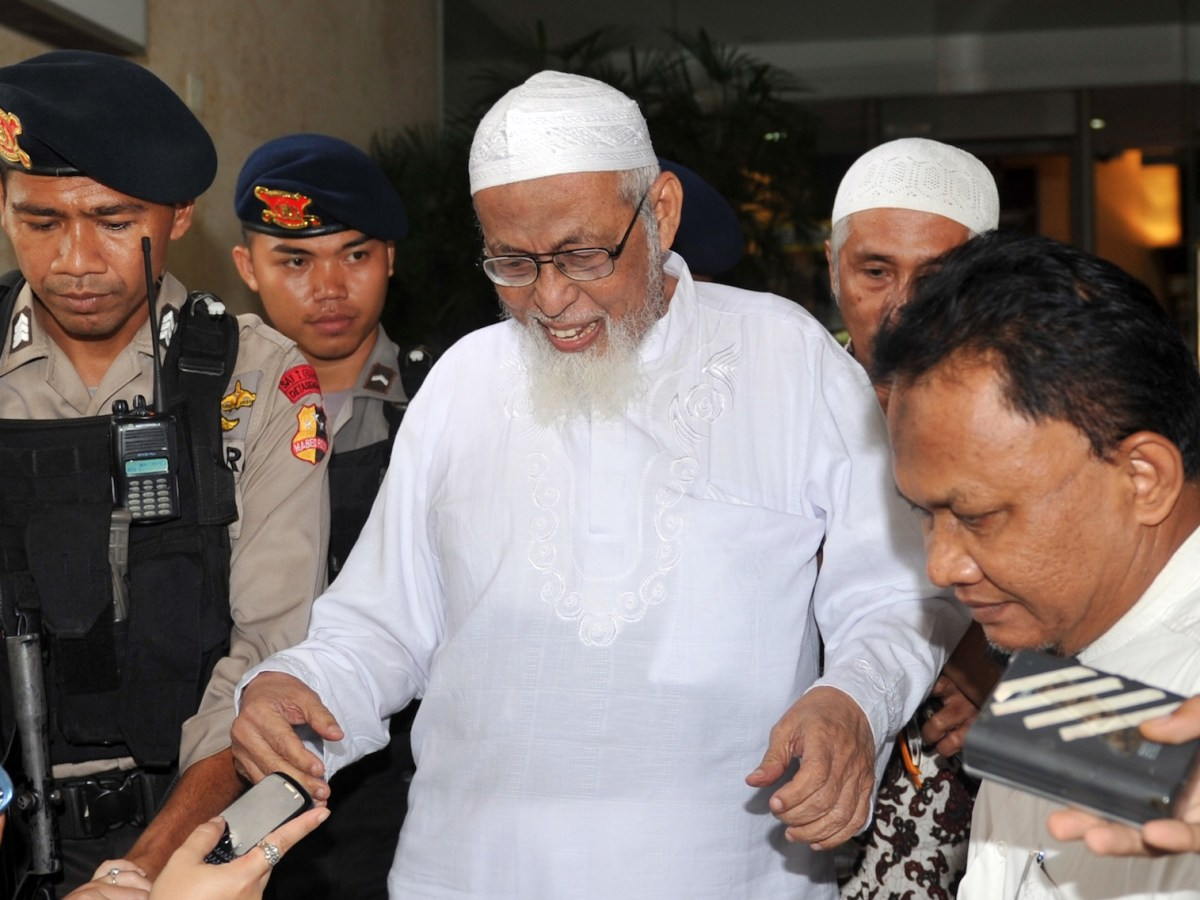 Muslim militant cleric Abu Bakar Bashir (C-in white) is guarded by Indonesian elite commandos as he leaves the police headquarters to undergo cataract surgery in Jakarta on February 29, 2012. Indonesia's top court on February 27 upheld a 15-year jail term against Islamist militant Abu Bakar Bashir for terrorist acts, reversing an earlier decision to slash the sentence to nine years.      AFP PHOTO / ADEK BERRY / AFP PHOTO / ADEK BERRY