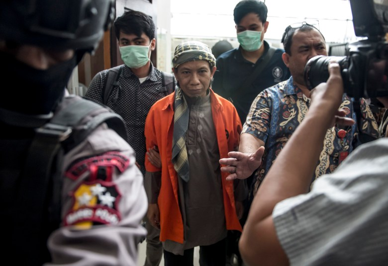 Indonesian armed police escort Indonesian radical cleric Aman Abdurrahman (C) into the South Jakarta courtroom in Jakarta on February 15, 2018, during his first appearance over his role in a 2016 suicide bombing.Abdurrahman, who is considered the de facto leader of all Islamic State (IS) supporters in Indonesia, appeared in court for his suspected role in masterminding a suicide bomb attack that killed eight people in Jakarta in 2016 and was claimed by IS. / AFP PHOTO / BAY ISMOYO