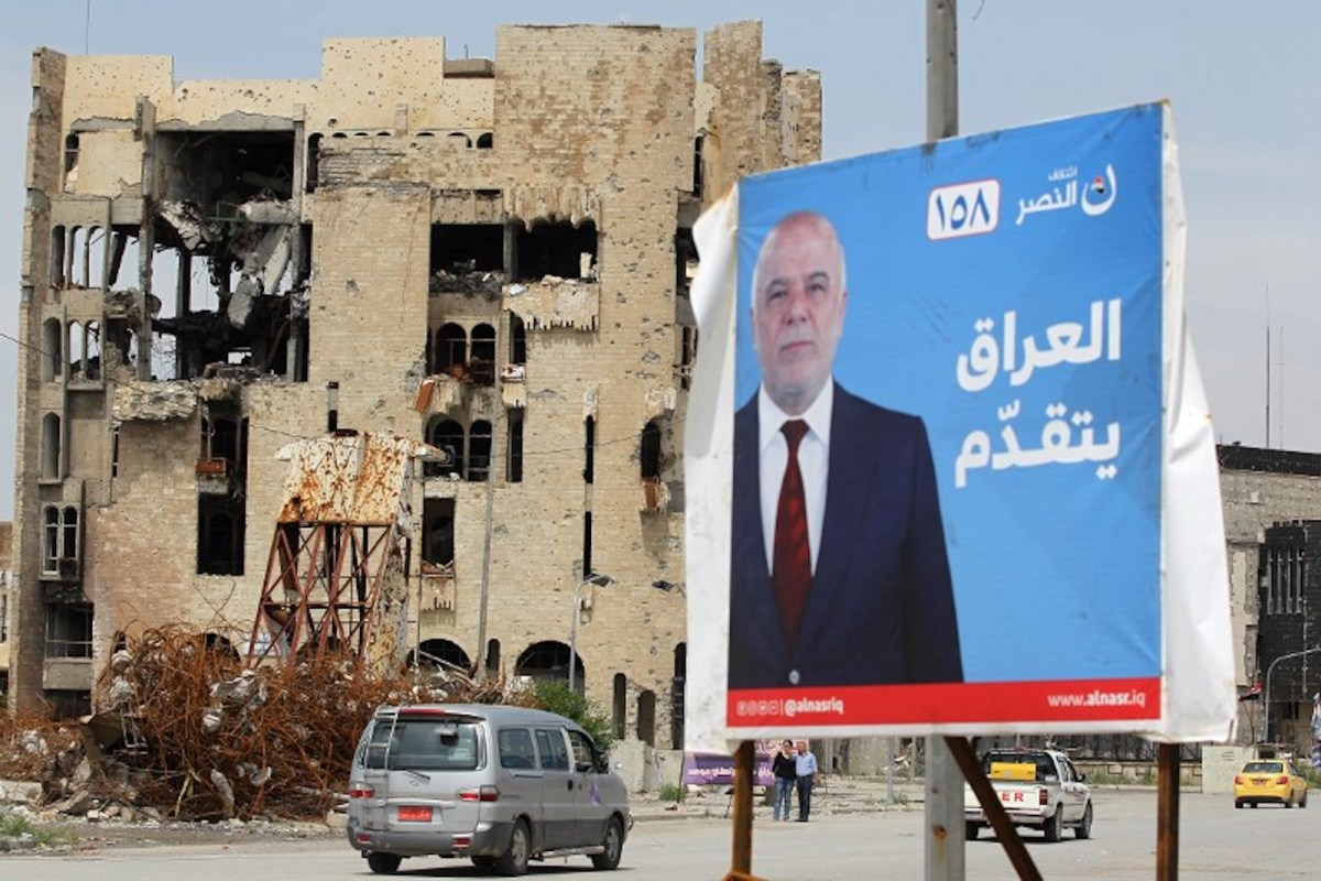 A car drives past an election poster of Iraq's Prime Minister in the old town of Mosul. Photo: AFP / Ahmad Al-Rubaye