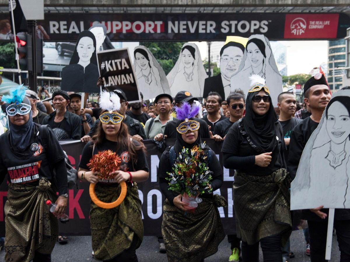 Protesters holding cut-out drawings depicting 1MDB-linked businessman Jho Low, murdered Mongolian translator Altantuya Shaariibuu and Prime Minister Najib's daughter, Nooryana Najwa. Photo: by Chris Jung/NurPhoto)