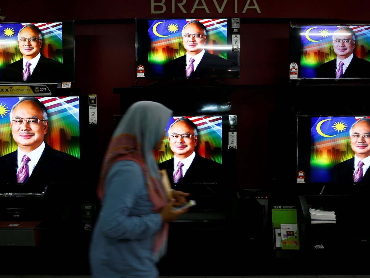A woman passes a live telecast of Malaysia's Prime Minister Najib Razak addressing the nation on the dissolution of Parliament at an electronics shop in Port Klang, Malaysia April 6, 2018. Photo: Reuters/Lai Seng Sin