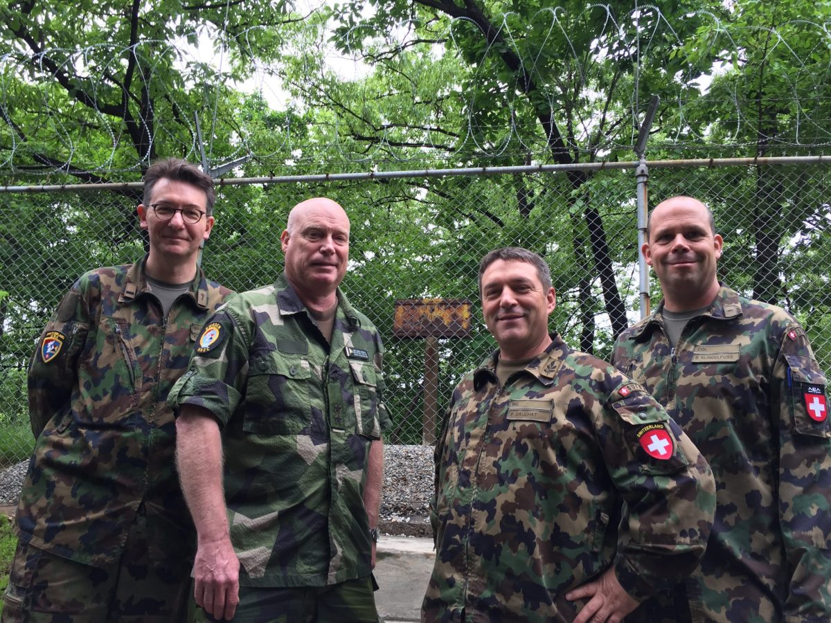 NNSC peackeepers at their camp ion Panmunjom stand in front of the marker of the MDL (military demarcation line - the border between the two Koreas in the center of the Demilitarized Zone). The signage facing South is in English and Korean; the signage facing North is in English and Chinese. From Left: Swiss Major Patrick Andres; Swedish Rear Admiral Anders Grenstad; Swiss Major General Patrick Gauchat; Swiss Colonel Beat Klingelfuss. Photo; Andrew Salmon/Asia Times
