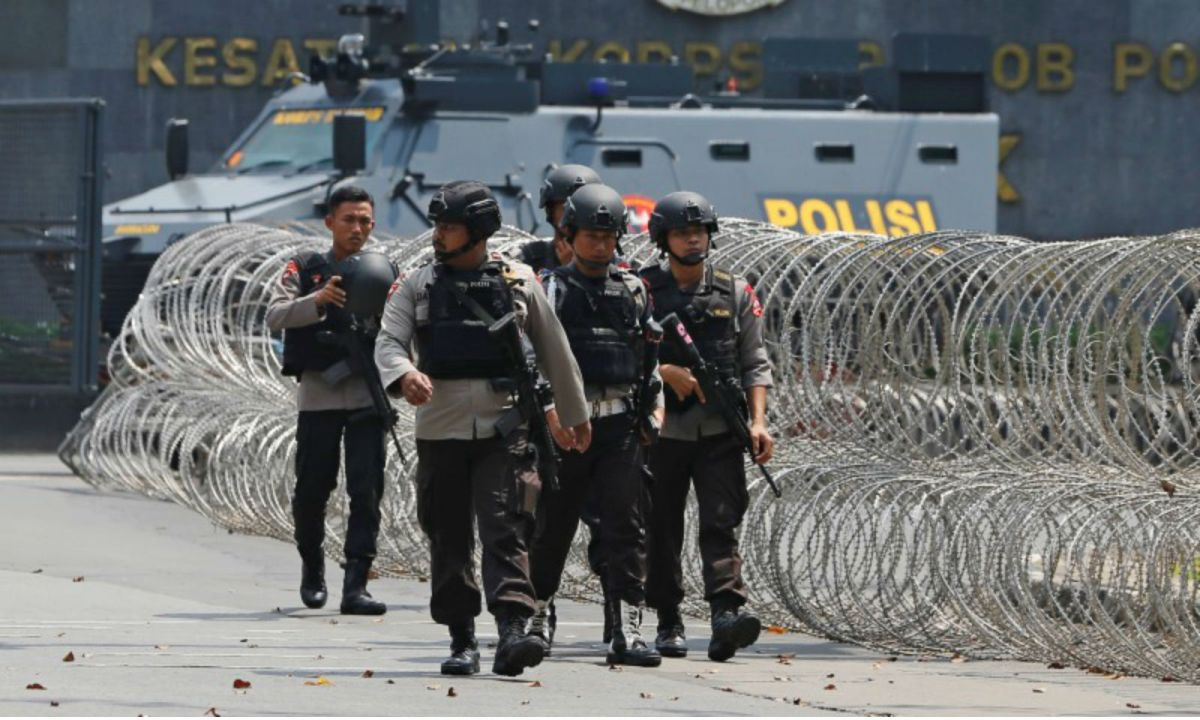 A group of mobile brigade policemen near an armored car at the Mobile Police Brigade headquarters in Depok, south of Jakarta. Photo: Reuters/Beawiharta