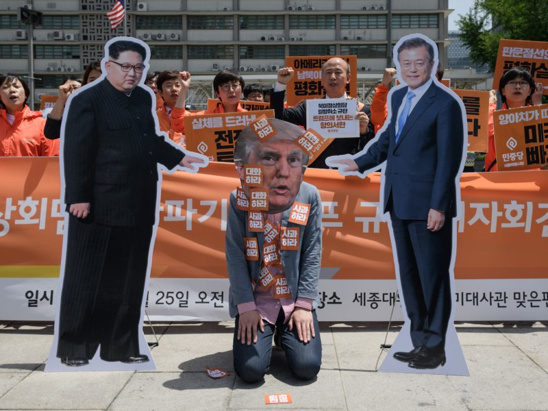 An anti-US protester wearing a face-mask depicting US president Donald Trump kneels between cardboard cutouts of North Korean leader Kim Jong Un, left, and South Korean leader Moon Jae-in during a rally calling for more dialogue between the three leaders, outside the US embassy in Seoul on May 25. Photo: AFP/ Ed Jones