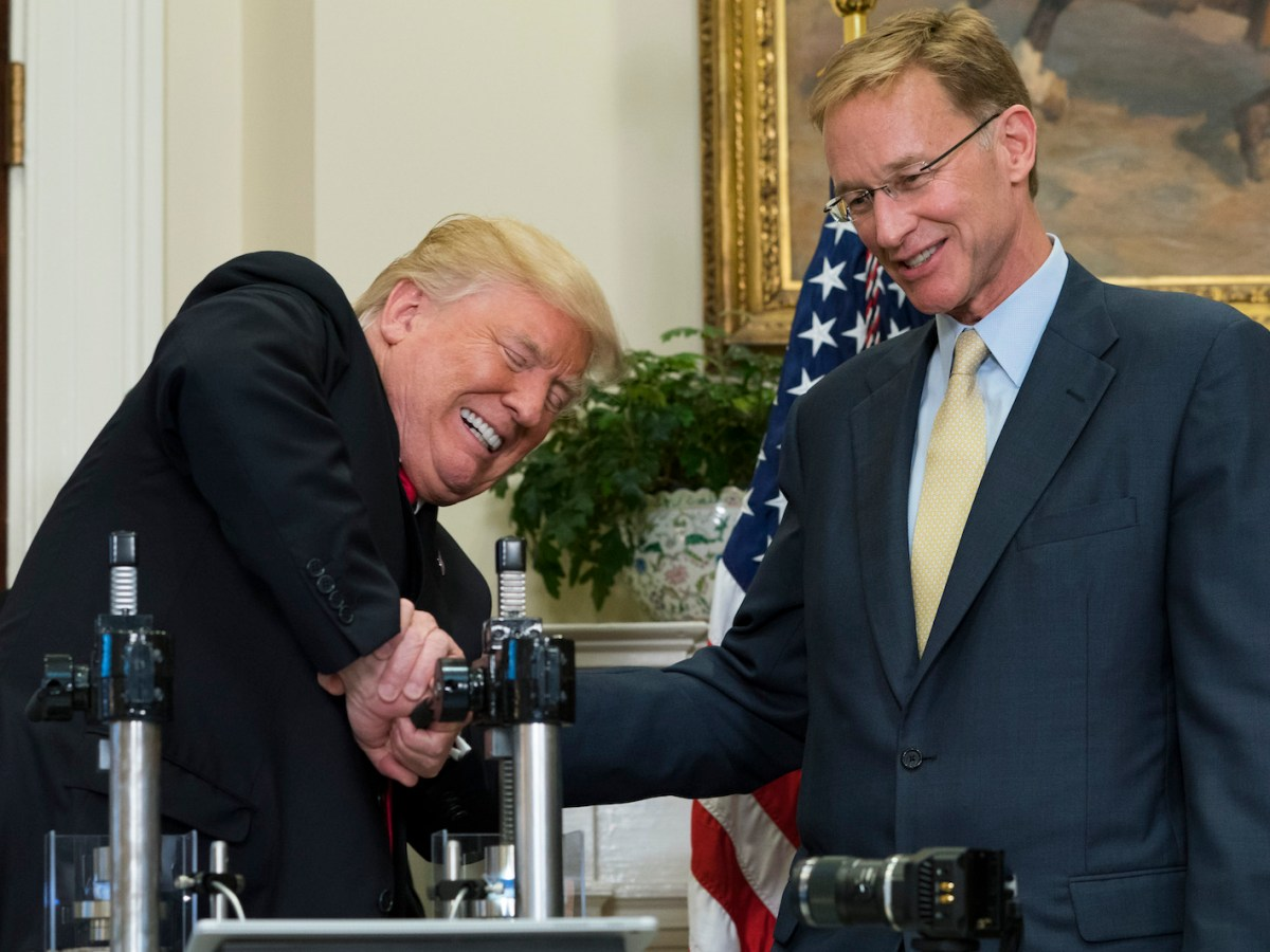 US President Donald Trump uses a machine to attempt to crush a newly designed 'Made in America' pharmaceutical glass bottle alongside Corning Chairman and CEO Wendell Weeks (R) during a Made in America Week event in the Roosevelt Room of the White House in Washington, DC, July 20, 2017. Photo: AFP/Saul Loeb
