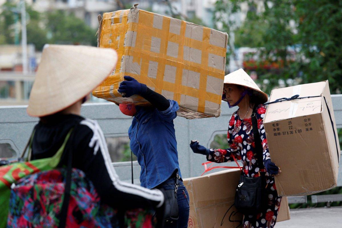 Vietnamese women carry goods on Bac Luan bridge, a border gate in Mong Cai city, Vietnam, April 12, 2018. Photo: Reuters/Kham