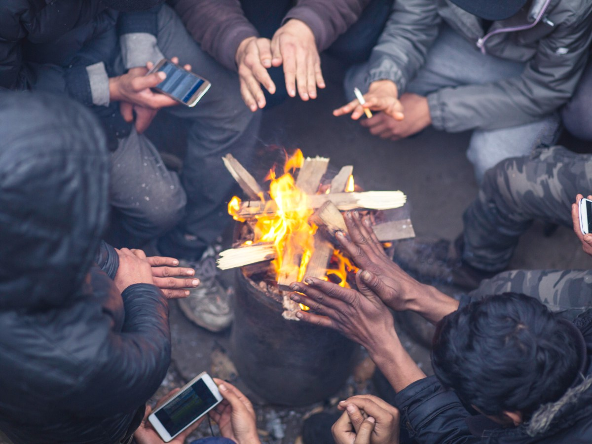 Refugees use smartphones while sheltering from the elements. Photo: iStock