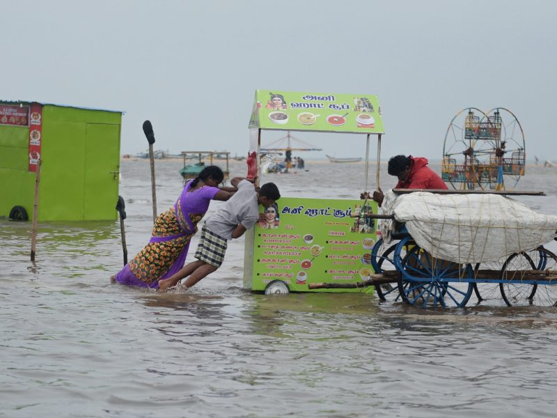 Indian women push a food cart stall in floodwater at Marina Beach on the Bay of Bengal coast after heavy rain in Chennai on November 3, 2017.The arrival of the northeast monsoon in recent days has brought heavy rains to southern India's Tamil Nadu, submerging parts of the state capital Chennai. Devastating floods following the northeast monsoon in south India in November and December 2015 killed more than 500 people and displaced almost two million others. Photo: AFP / Arlin Sankar