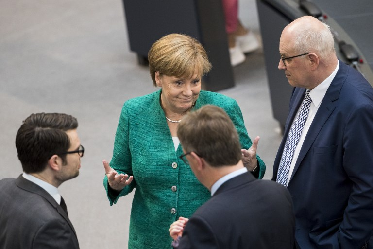 German Chancellor Angela Merkel greeting Parliamentary group leader of CDU/CSU Volker Kauder in the Bundestag German Lower House of Parliament on Thursday. Photo: NurPhoto via AFP