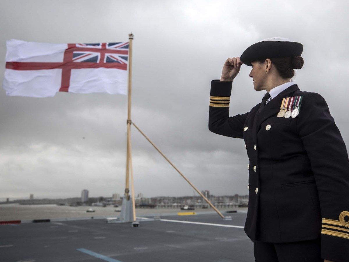 A naval officer looks up at the fluttering White ensign flag hoisted at the stern during the Commissioning Ceremony for the Royal Navy aircraft carrier HMS Queen Elizabeth at HM Naval Base in Portsmouth, southern England on December 7, 2017.Her Majesty The Queen, accompanied by Her Royal Highness The Princess Royal, attended the Commissioning Ceremony of the aircraft carrier HMS Queen Elizabeth, the largest warship ever built for the Royal Navy. / AFP PHOTO / POOL / RICHARD POHLE