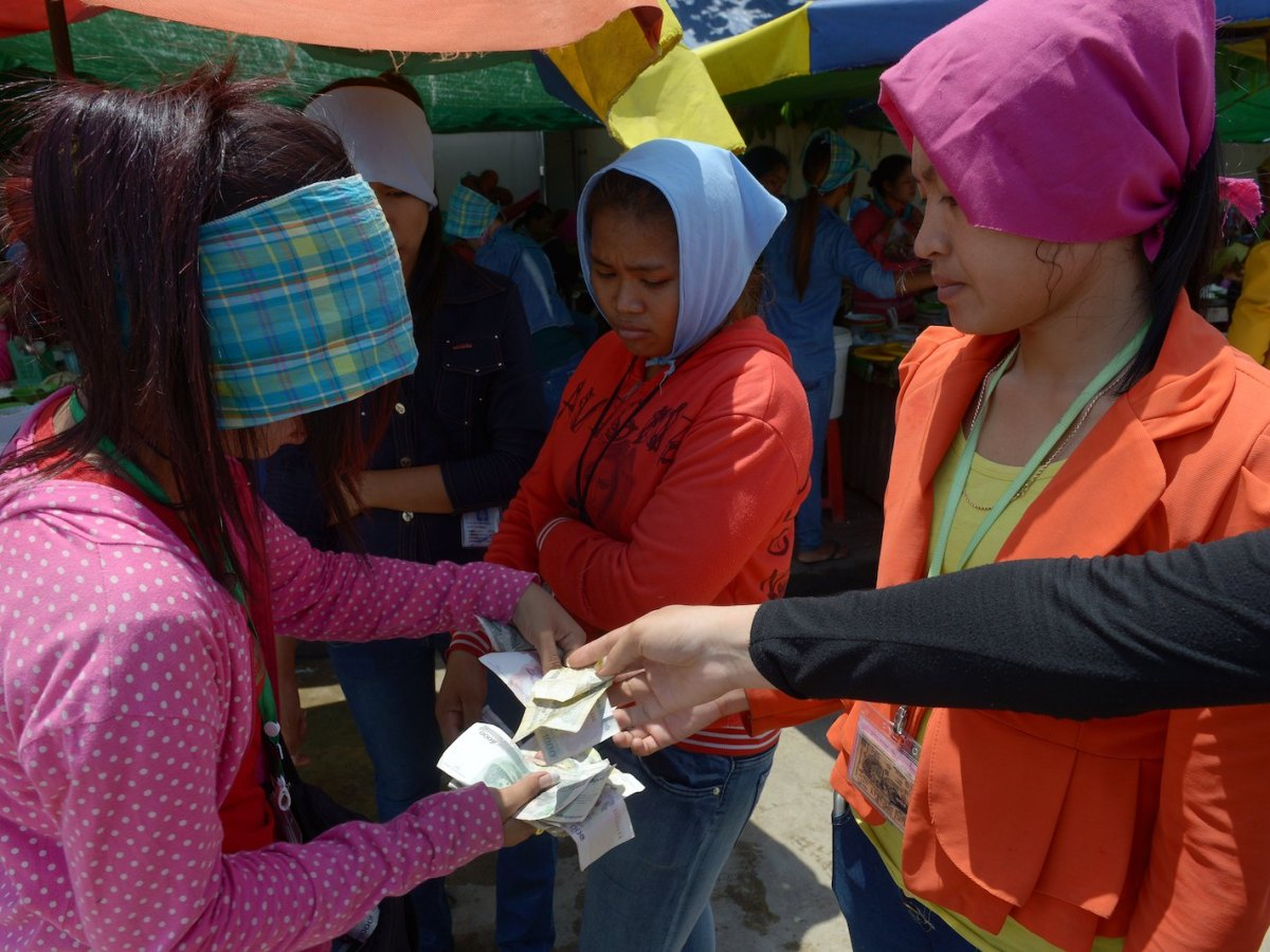 A Cambodian garment worker gets pay for her lunch in front of a factory in Phnom Penh. Women in worksites such as these are often targets of sexual harassment. Photo: AFP/ Tang Chhin Sothy