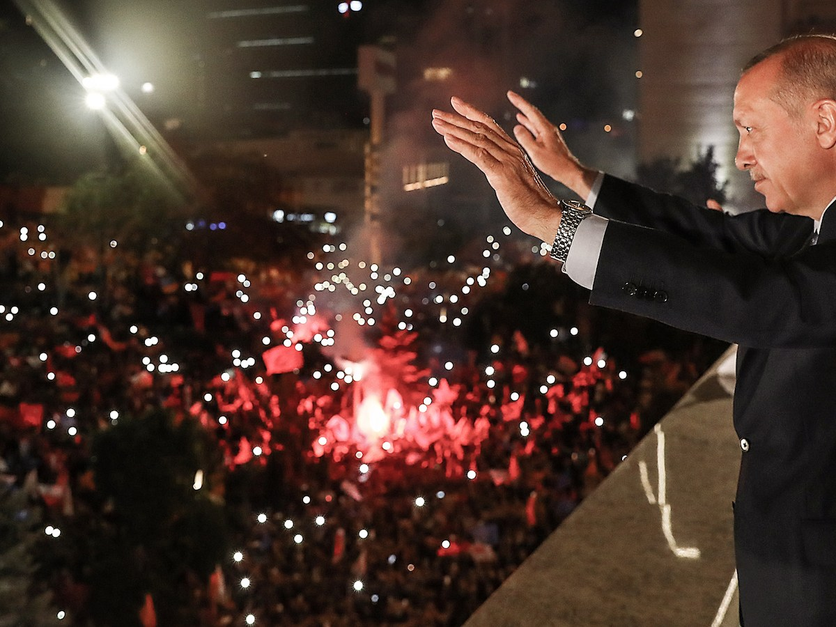 Turkish President Tayyip Erdogan waves to supporters from a balcony at the AK Party headquarters in Ankara, on June 24 as they celebrate him winning five more years in office with sweeping new powers after a decisive election victory. Photo: AFP / Turkish Presidential Press Office / Kayhan Ozer