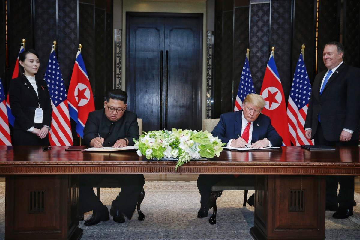 The two leaders sign the summit declaration, watched by the North Korean leader's sister and US Secretary of State Mike Pompeo. Photo: Pool / Kevin Lim / Straits Times