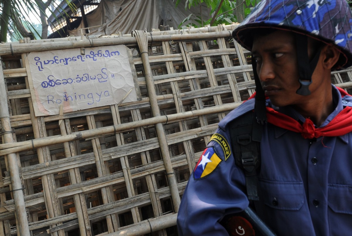 A Myanmar police officer looks at a notice displayed on a fence at a Muslim household during a census taking at the village of Theechaung on the outskirts of Sittwe in the western Myanmar state of Rakhine, April 1, 2014. Photo: AFP/ Soe Than Win