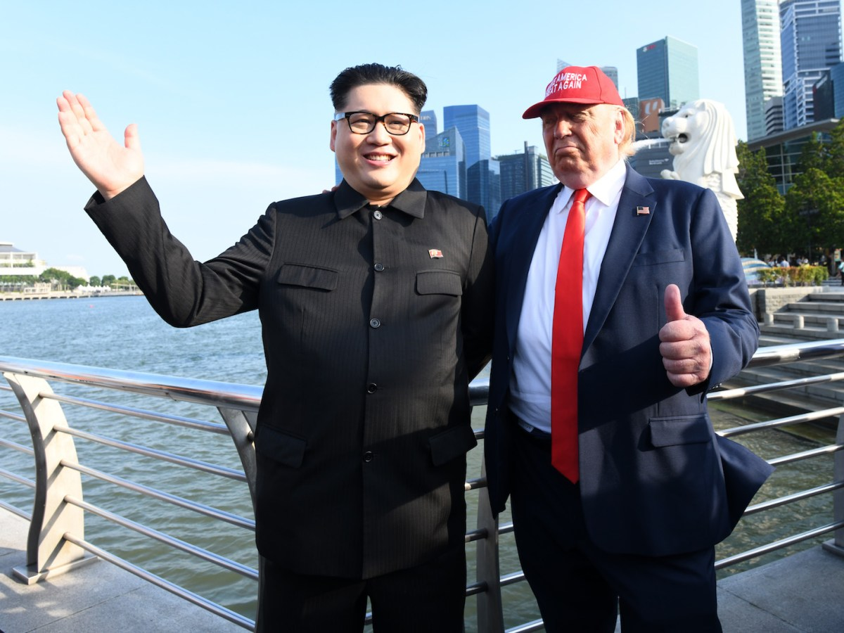 North Korean leader Kim Jong-un impersonator Howard X (L) and Donald Trump impersonator Dennis Alan (R) stand along the Merlion park in Singapore, June 8, 2018: AFP/Roslan Rahman