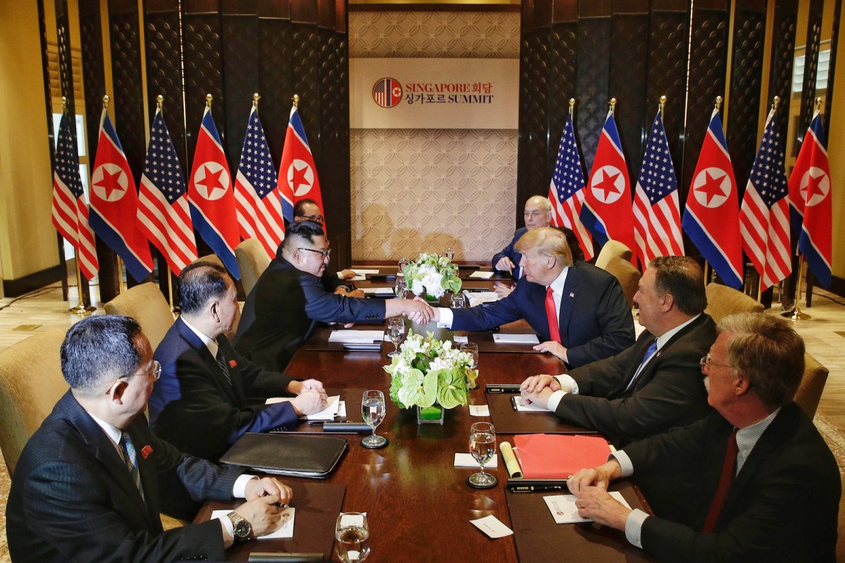 Kim Jong-un and Donald Trump shake hands across the table during morning talks at their summit in Singapore. Photo: Pool/ Kevin Lim/ Straits Times