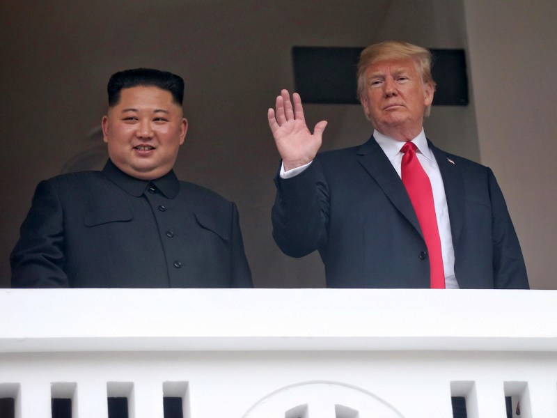 The two leaders pose for photographers from a balcony on the Capella Hotel in Singapore. Photo: Pool/ Kevin Lim/ Straits Times