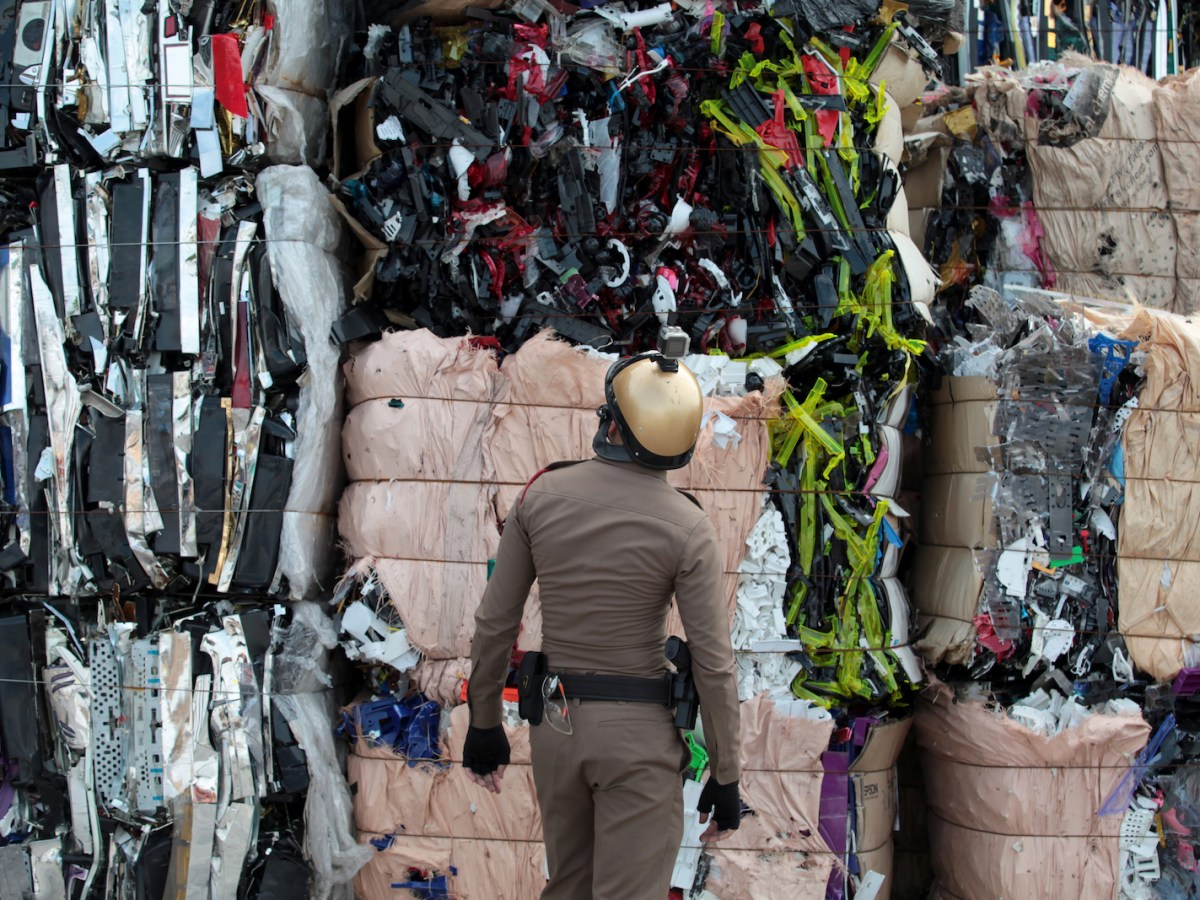 A policeman inspects piles of electronic waste at a factory in Klong Luang near Bangkok. The factory owner was charged with disposing of waste without permission and illegally employing foreign workers. Photo: AFP/ Bangkok Post/ Chanat Katanyu