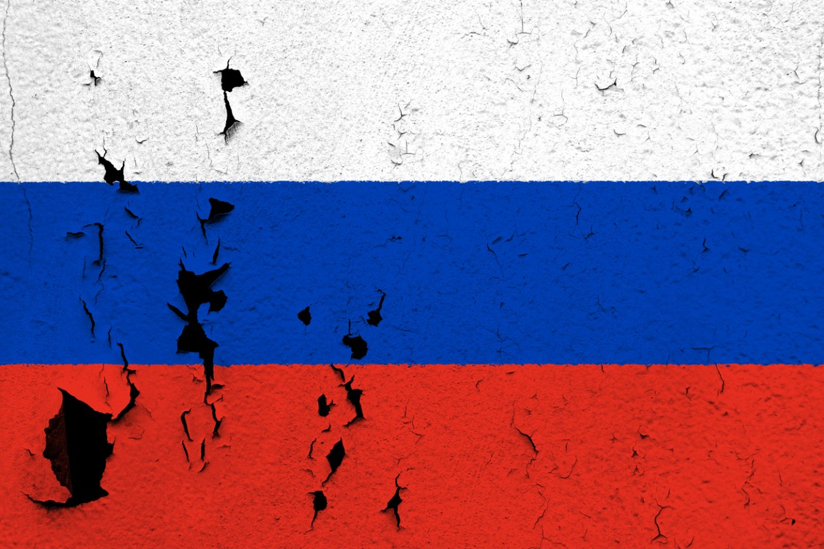 The flag of Russia painted on a cracked and peeling wall.