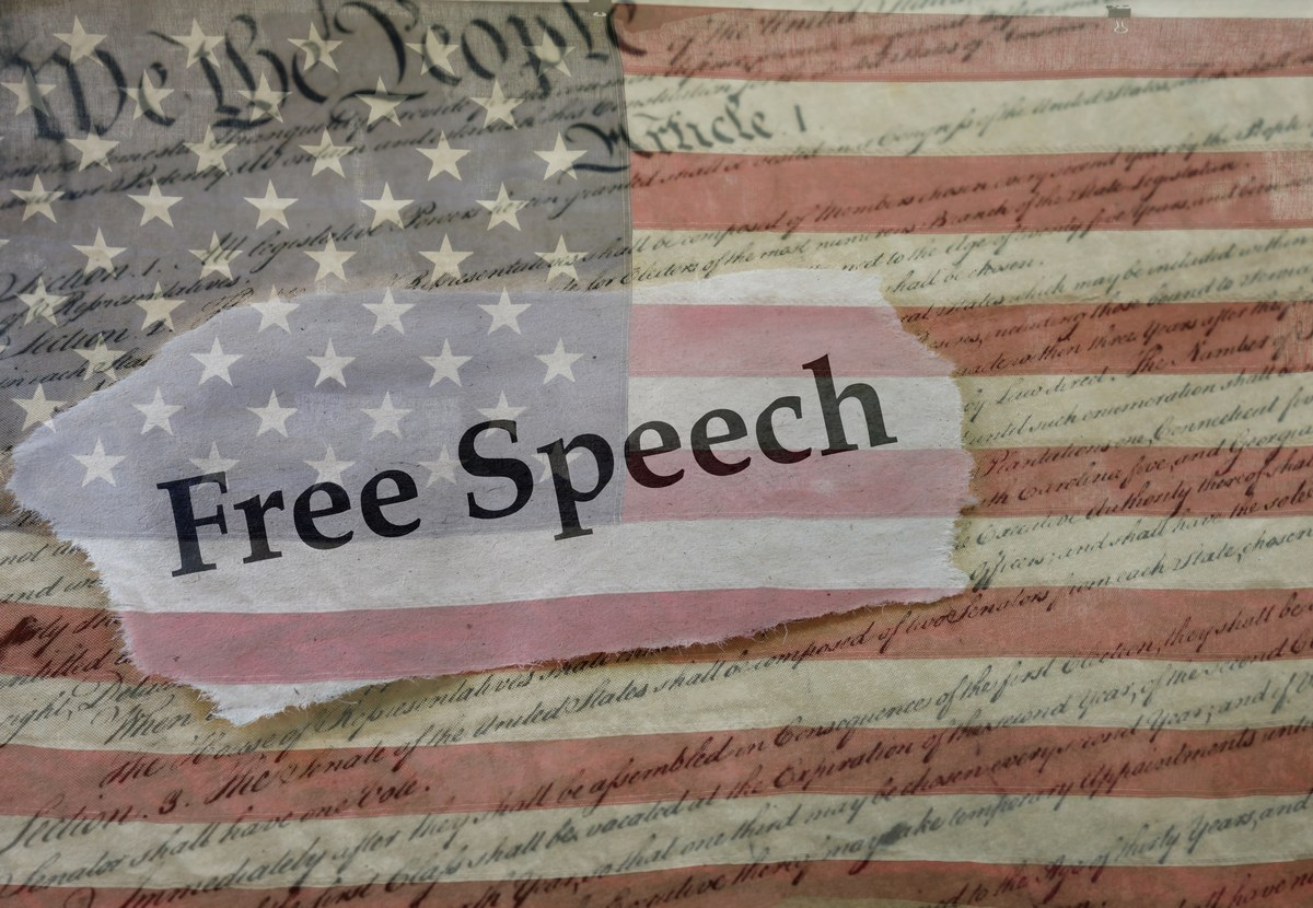 Free Speech news headline on a copy of the  United States Constitution and the US flag. Photo: iStock