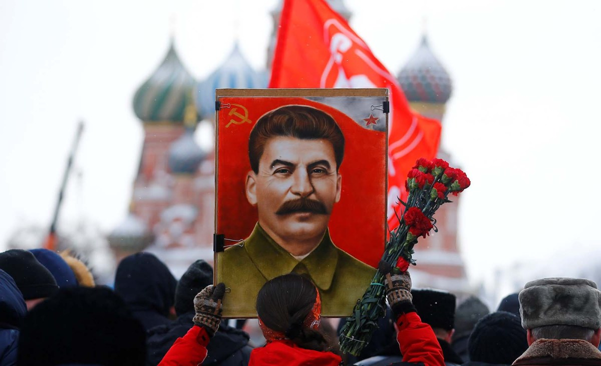 A woman holds a poster of Joseph Stalin during a commemoration ceremony to mark the 65th anniversary of Stalin's death at the Red Square in Moscow on March 05, 2018. Photo: Anadolu Agency/Sefa Karacan