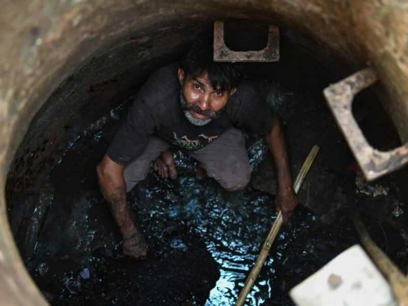 An Indian manual scavenger looks on as he cleans a manhole in the old quarters of New Delhi on March 21, 2018. Photo: AFP/Chandan Khanna
