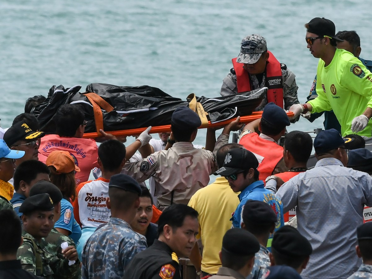 Thai rescue personnel carry a bag at Chalong pier in Phuket on July 6 bearing the body of a passenger recovered from the sea after a tourist boat sank late the previous day. Photo: AFP/ Mohd Rasfan