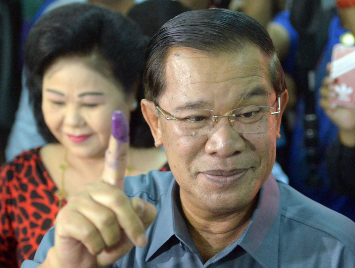 Cambodian Prime Minister Hun Sen (R) raises his inked finger at a polling station after voting during a general election in 2013. Photo: AFP/Tang Chhin Sothy