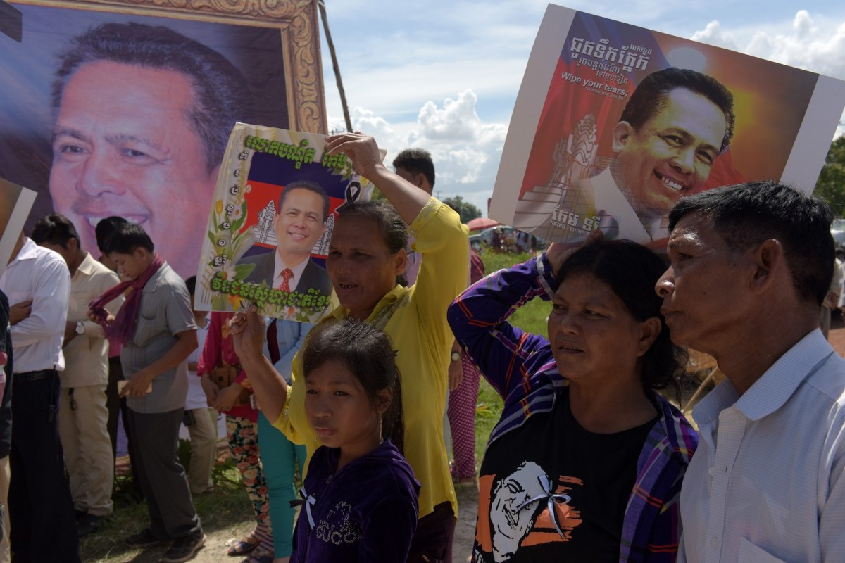 Cambodians hold images of prominent Cambodian critic Kem Ley at his mother's home in Takeo province during the first anniversary of his murder. Photo: AFP/Tang Chhin Sothy