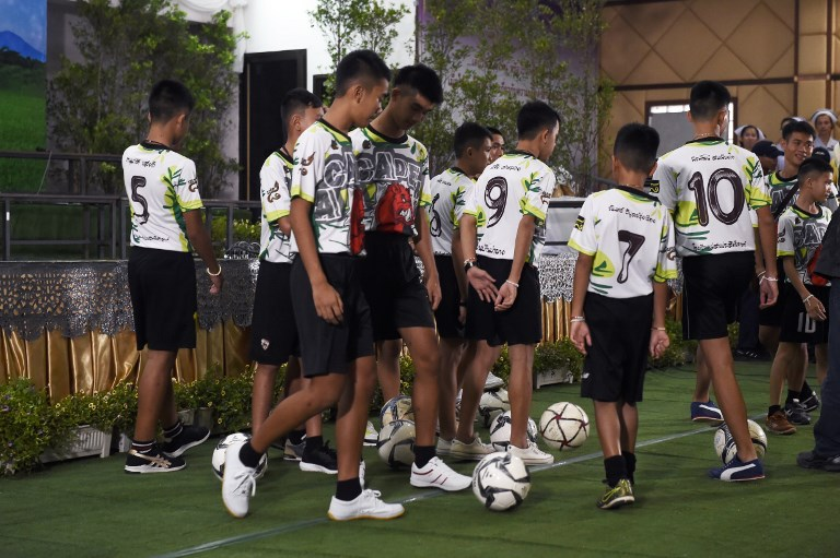 Some of the 12 boys dramatically rescued from deep inside a Thai cave after being trapped for more than two weeks play with soccer balls before a press conference in Chiang Rai on July 18, 2018, after their discharge from hospital. Photo: AFP / Lillian Suwanrumpha