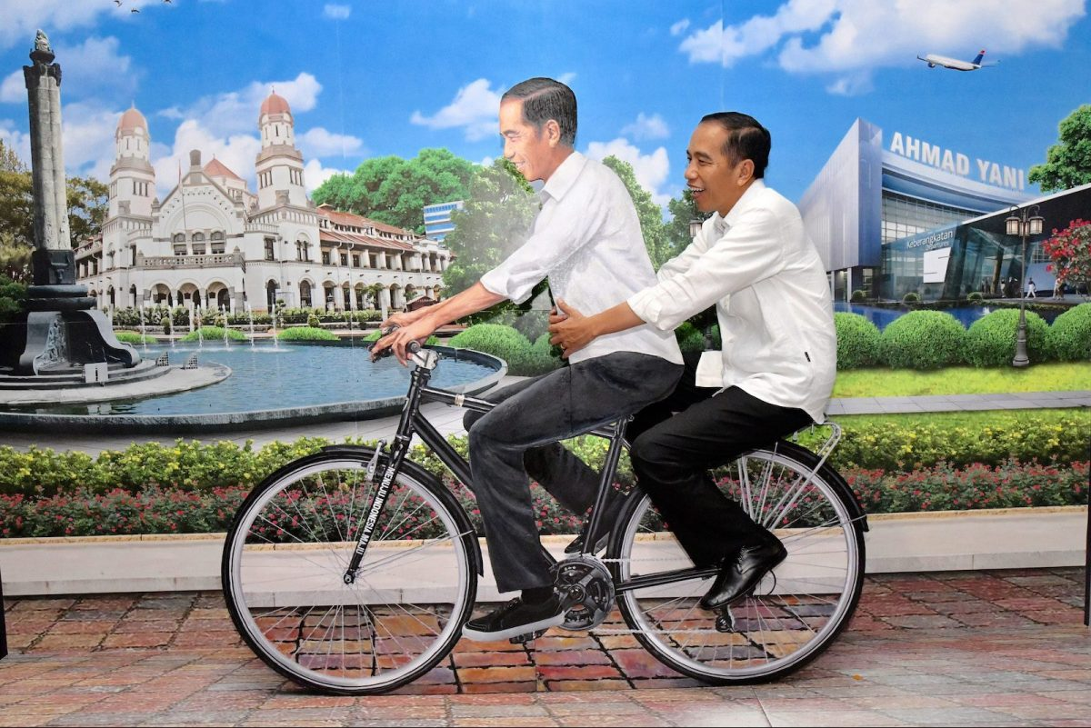 Indonesian President Joko Widodo (R), sits on the back side of a decoration bicycle with a picture of himself at a newly opened terminal at Semarang city airport, in Central Java, on June 7, 2018. Photo: AFP/ Presidential Palace/Handout
