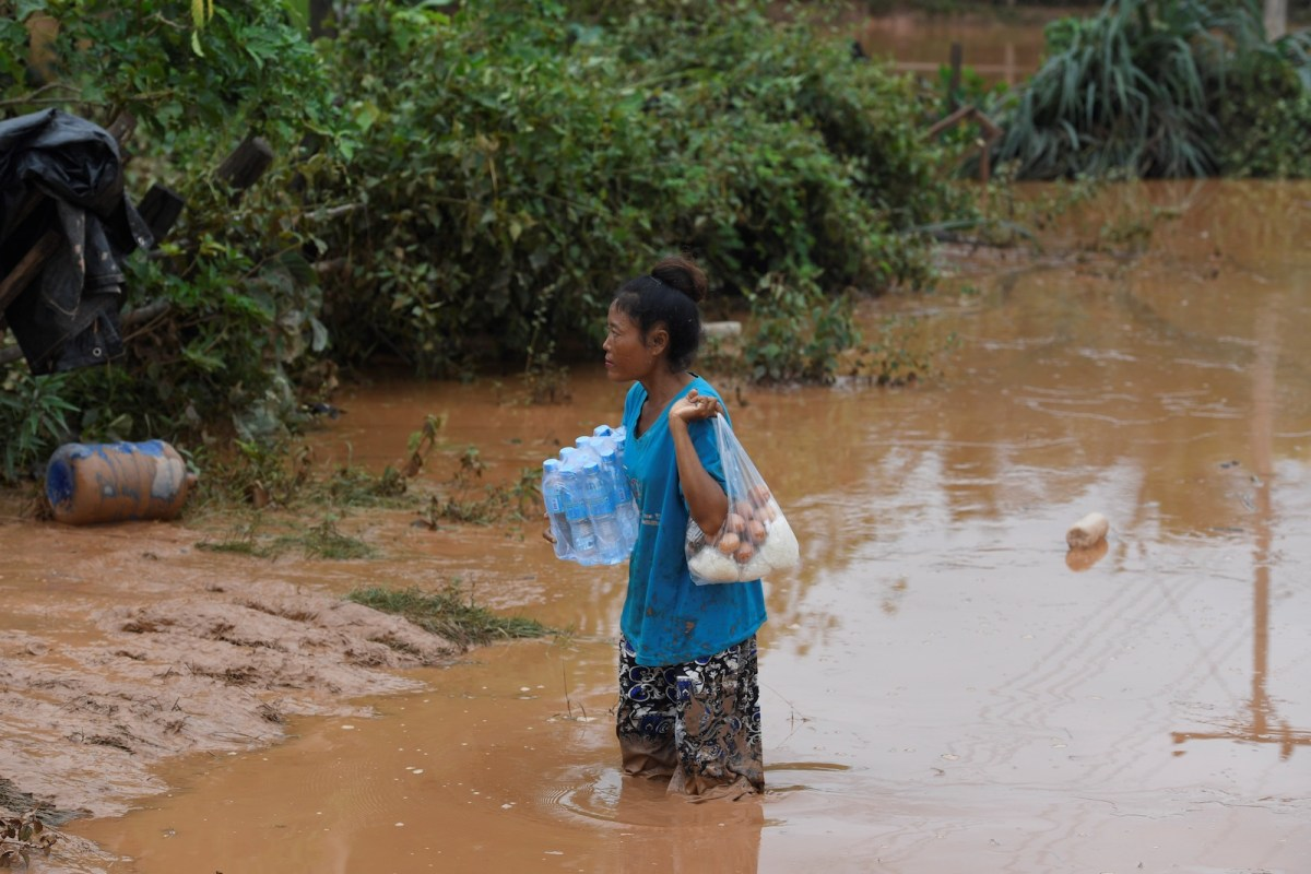 A flood victim with food from relief personnel in Sanamxai, Attapeu province, on July 27, 2018. Rescuers seek to find scores of Laotians still missing after entire villages were washed away. Photo: AFP/ Nhac Nguyen