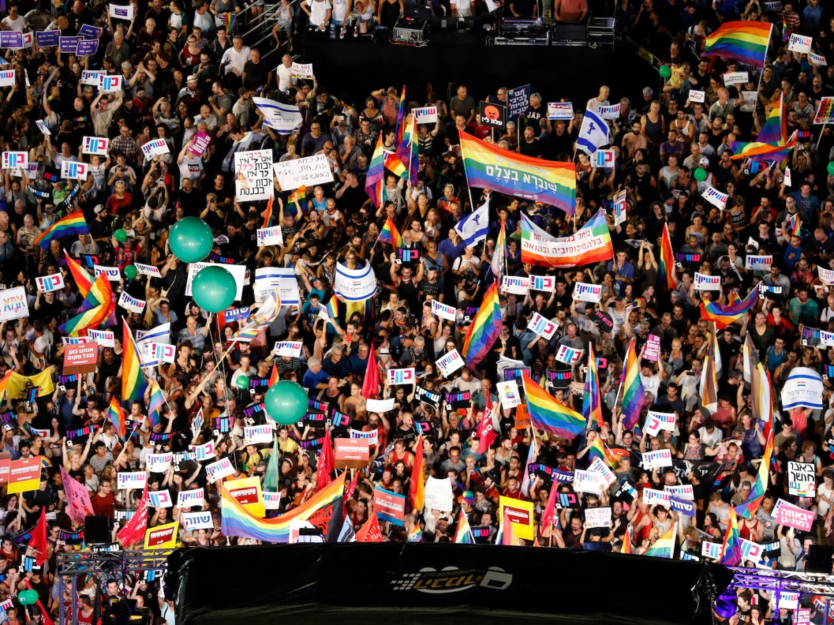 Israelis attend a rally in Tel Aviv on July 22 to protest over a new surrogacy law that does not include gay couples. It came after parliament approved surrogacy for single women or those unable to bear children, without granting such a right to same-sex couples or single men. Photo: AFP / Jack Guez