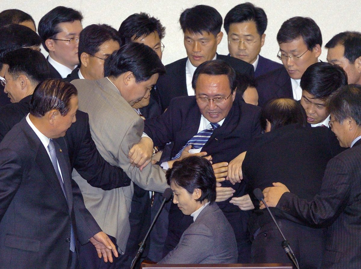 Roh Hoe-Chan (C) gets removed from the speaker's chair at the National Assembly on November 23, 2005, during a heated debate. Roh, however, was one of the more moderate politicians in South Korea. Photo: AFP/Jung Yeon-Je