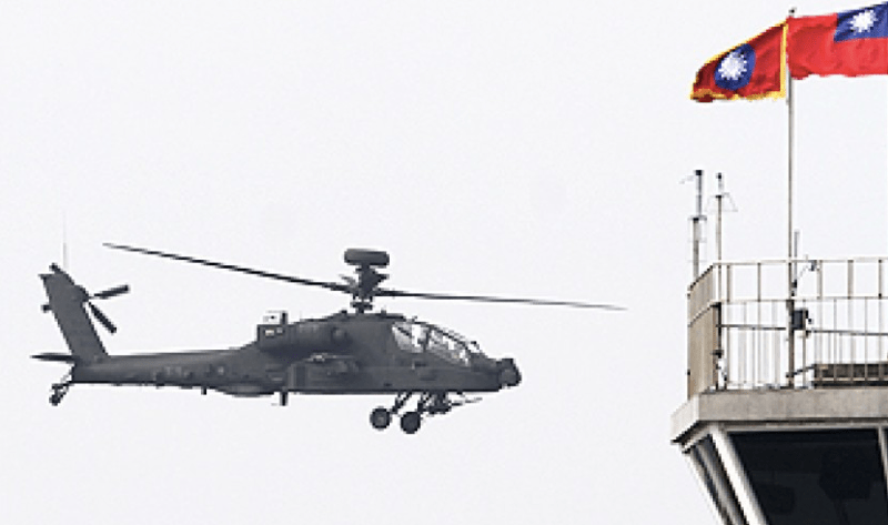 An Apache assault helicopter flies past Taiwanese flags. Photo: AFP