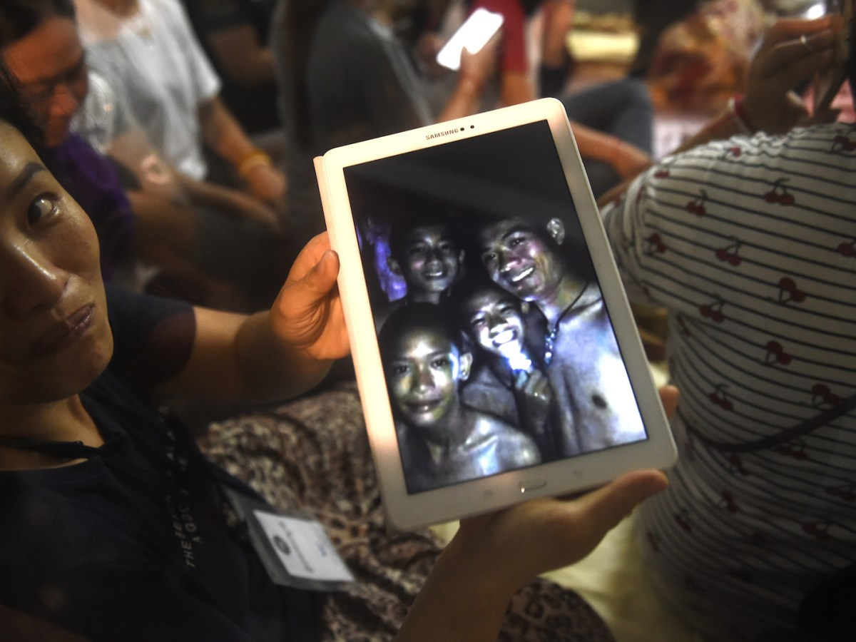 A family member shows a picture of four of the 12 missing boys near the Tham Luang cave in Mae Sai on July 2, 2018. Photo: AFP/ Lillian Suwanrumpha