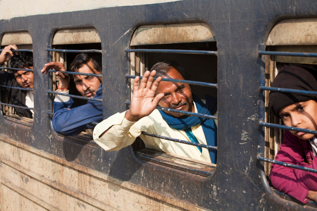 Tundla, India, November 26: four people, three men and a boy, sitting in a departing train, the man waving good bye. Photo: iStock