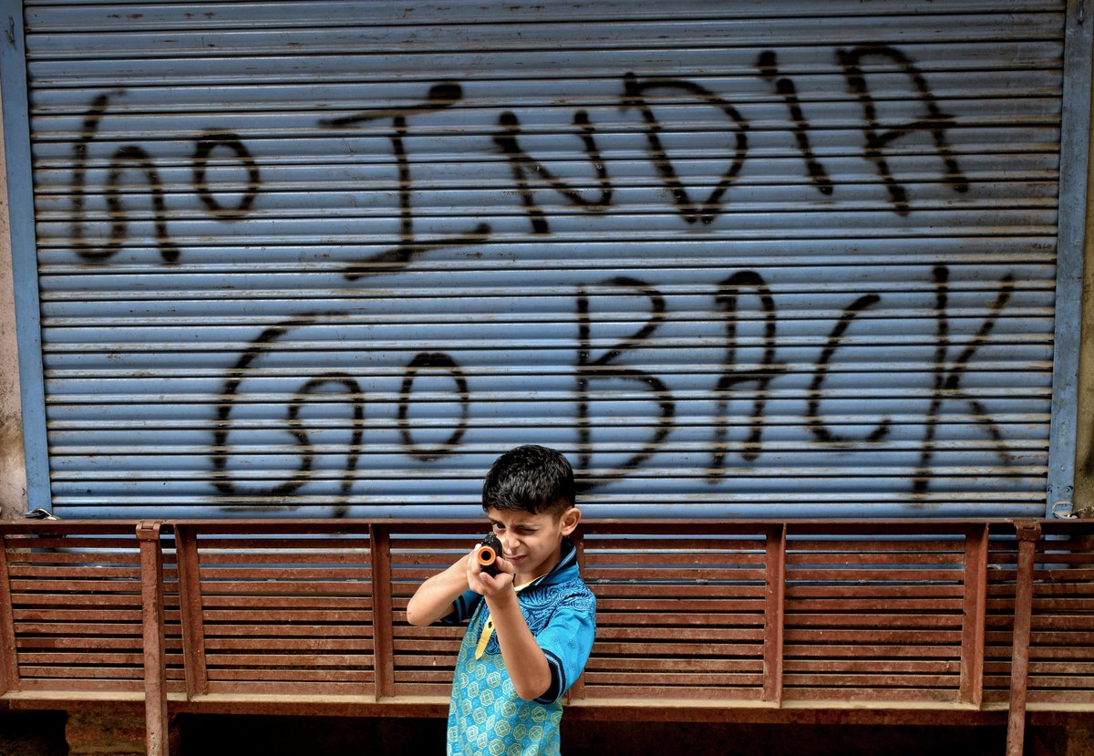A Kashmiri boy poses for a picture past a Graffiti marked on closed shutter of a shop during a shutdown in Srinagar, the summer capital of Jammu & Kashmir. Photo: iStock