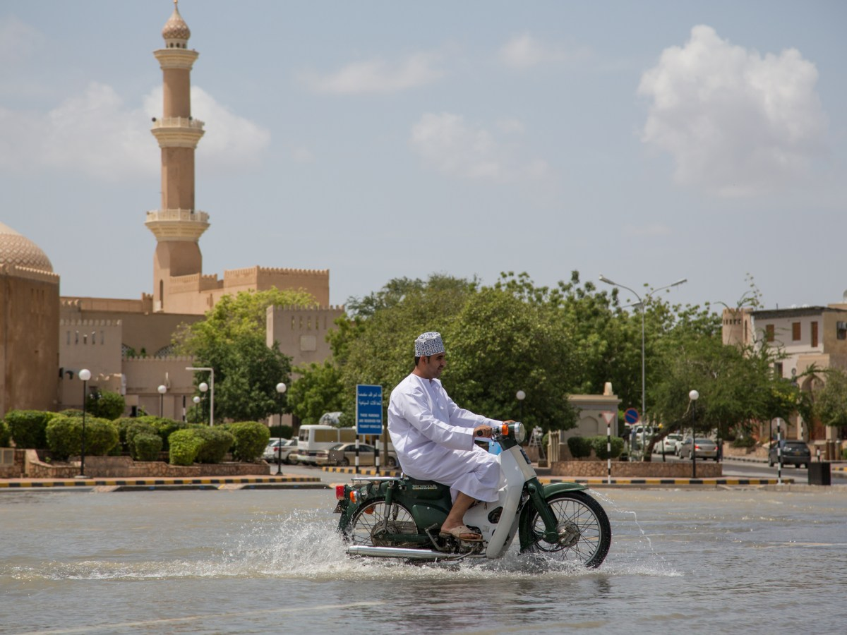 An Omani man drives a motorcycle through the flooded streets of Nizwa, Oman, after monsoon rains touched down. Photo: iStock