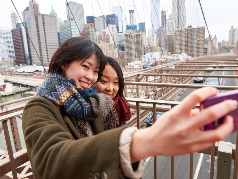 Two Chinese tourists take pictures on the Brooklyn Bridge in New York City. Photo: Shutterstock
