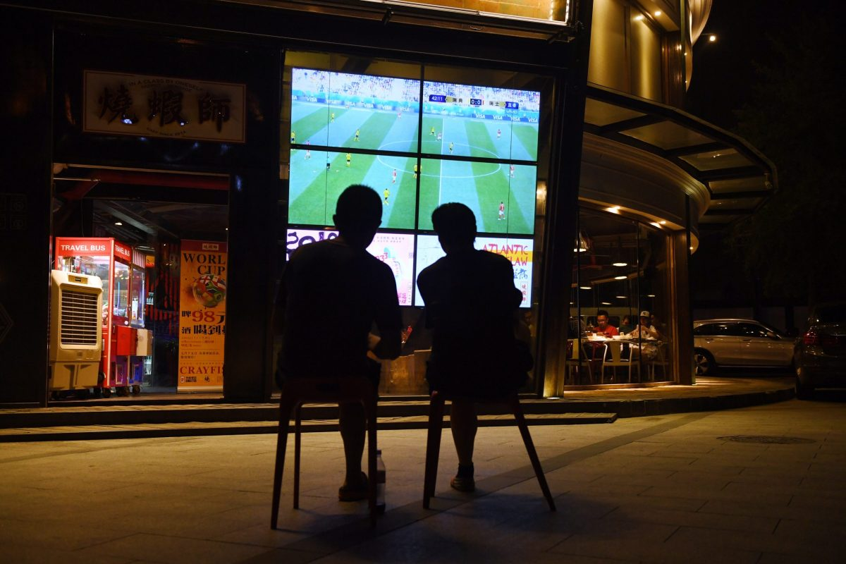 Two men watch a 2018 Russia World Cup football match on a TV screen outside a restaurant in Beijing. Photo: AFP/Greg Baker
