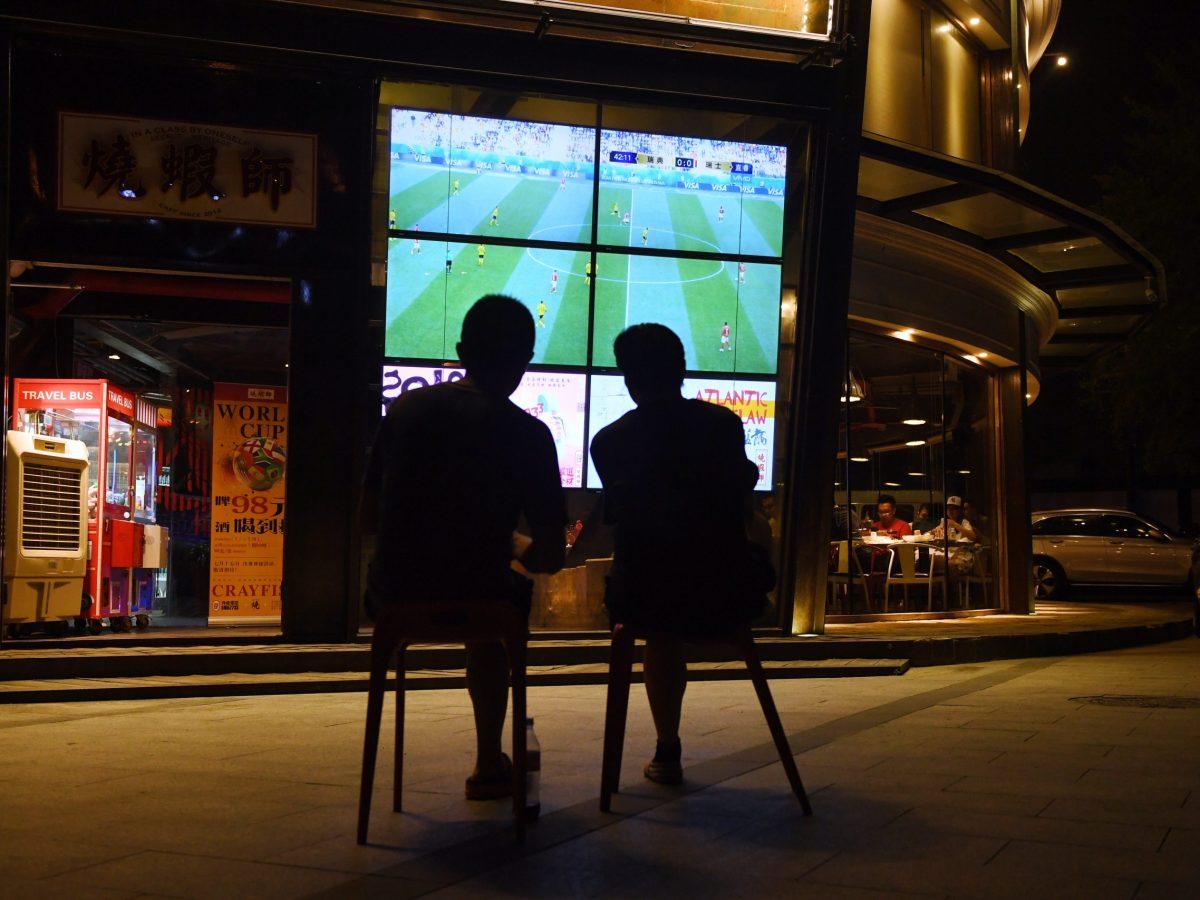 Two men watch a 2018 Russia World Cup football match on a TV screen outside a restaurant in Beijing. Photo: AFP/Greg Baker