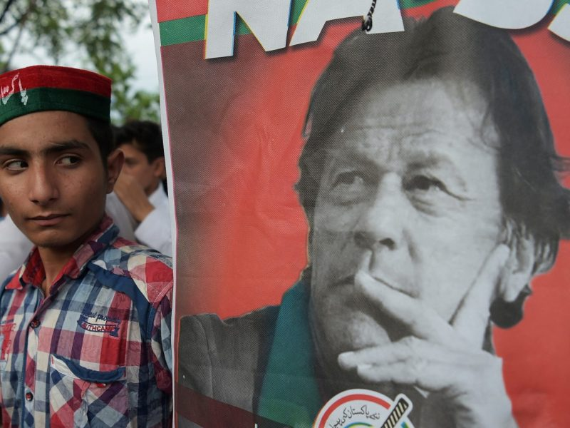 A supporter of Imran Khan, head of the Pakistan Tehreek-e-Insaf (PTI) party, stands next to a poster showing the former cricket star turned politician. AFP / Aamir Qureshi