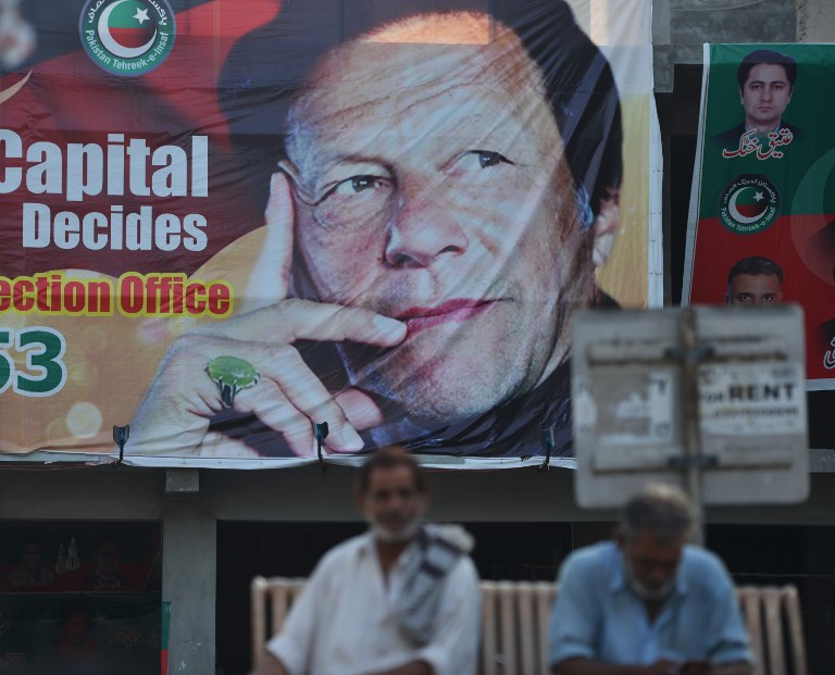 Pakistani men sit near a poster of Pakistan's cricketer-turned politician and head of the Pakistan Tehreek-e-Insaf (Movement for Justice) party Imran Khan, in Islamabad on July 30, 2018.Pakistan's World Cup cricket hero Imran Khan is set to become prime minister of the nuclear-armed nation of 207 million, with an economy inching toward crisis and perennial conflict on its borders. Running the country will take considerable statecraft from Khan's relatively inexperienced party. He brings charisma, international name recognition and a sizeable election victory, though not enough to form a majority government. Photo: AFP
