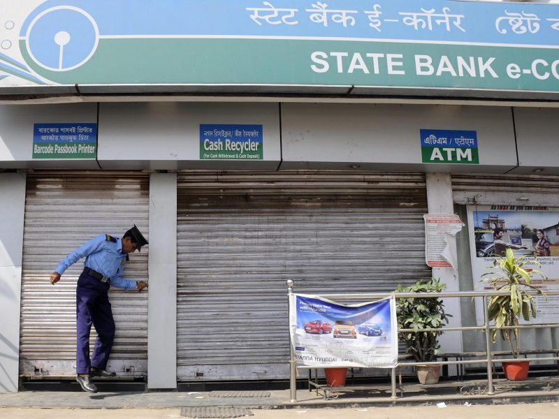 An Indian security guard pulls down the shutters of a state bank's ATM branch during a nationwide bank strike in Agartala, the capital of the northeastern state of Tripura, on February 28, 2017. / AFP PHOTO / Arindam DEY